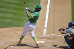 Oakland Athletics' Khris Davis swings for a two run single off Texas Rangers' Mike Minor in the fourth inning of a baseball game Thursday, Aug. 6, 2020, in Oakland, Calif. (AP Photo/Ben Margot)