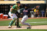Cleveland Indians' Daniel Johnson, right, slides into home plate past Oakland Athletics catcher Sean Murphy, left, to score a run on a single by Bradley Zimmer during the fifth inning of a baseball game Sunday, July 18, 2021, in Oakland, Calif. (AP Photo/Tony Avelar)