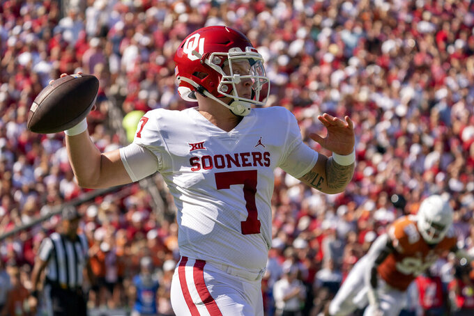 Oklahoma quarterback Spencer Rattler (7) throws downfield against Texas during the first half of an NCAA college football game at the Cotton Bowl, Saturday, Oct. 9, 2021, in Dallas. (AP Photo/Jeffrey McWhorter)