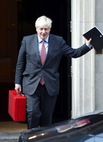 Britain's Prime Minister Boris Johnson leaves 10 Downing Street, London, Monday Sept. 21, 2020. Britain's chief medical officers have raised the nation's official COVID-19 alert level, meaning the virus is in general circulation and the transmission is high. Boris Johnson is expected to announce further curbs Tuesday to slow the spread of the virus. (Yui Mok/PA via AP)