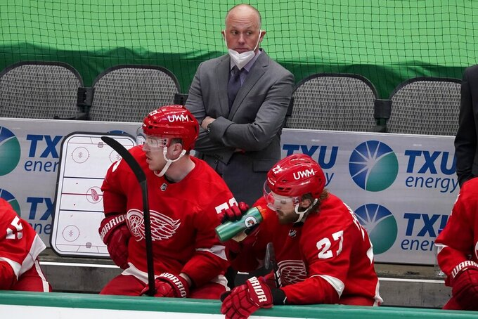 File-This April 20, 2021, file photo shows Detroit Red Wings head coach Jeff Blashill, rear, Adam Erne (73) and Michael Rasmussen (27) watching play against the Dallas Stars. The Red Wings are sticking with Blashill for their rebuild. General manager Steve Yzerman made the announcement Tuesday,  May 18, 2021, giving Blashill a contract extension despite a five-year postseason drought and a career record of 172-221-62.  (AP Photo/Tony Gutierrez, File)