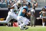 Jacksonville Jaguars quarterback Gardner Minshew, right, tries to scramble past New Orleans Saints defensive end Marcus Davenport (92) during the first half of an NFL football game, Sunday, Oct. 13, 2019, in Jacksonville, Fla. (AP Photo/Phelan M. Ebenhack)