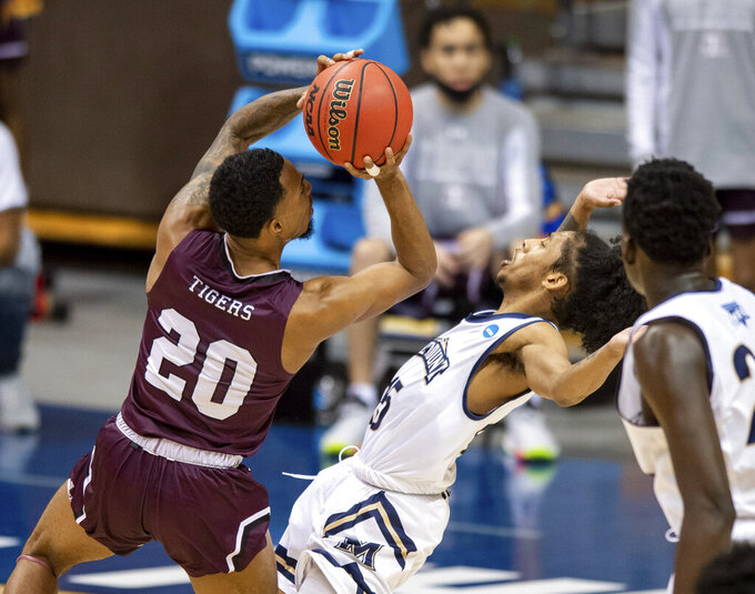 Texas Southern guard Michael Weathers (20) drives the ball into the defense of Mount St. Mary's guard Damian Chong Qui (15) during the second half of a First Four game in the NCAA men's college basketball tournament Thursday, March 18, 2021, in Bloomington, Ind. (AP Photo/Doug McSchooler)