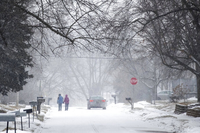 Two people hold hands while walking south on Madison Street toward 27th Avenue in Bellevue, Neb., during a winter storm warning on Monday, Jan. 25, 2021. (Chris Machian/Omaha World-Herald via AP)