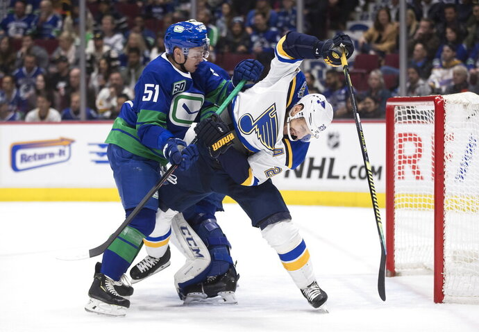 Vancouver Canucks' Troy Stecher (51) checks St. Louis Blues' Alexander Steen (20) during the first period of an NHL hockey game Tuesday, Nov. 5, 2019, in Vancouver, British Columbia. (Darryl Dyck/The Canadian Press via AP)