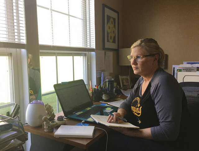 This April 3, 2020 photo shows realtor Michelle Bushée posing at her desk while working from her home in Pittsburgh, Pa. Bushee has always been an avid planner. Her weeks used to be very busy but now the entire month of April is empty. (Nick Bushée via AP)