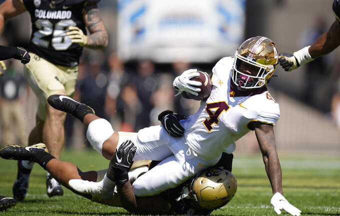 Minnesota running back Mar'Keise Irving, top, is dragged down by Colorado defensive lineman Janaz Jordan in the second half of an NCAA college football game Saturday, Sept. 18, 2021, in Boulder, Colo. Minnesota won 30-0. (AP Photo/David Zalubowski)