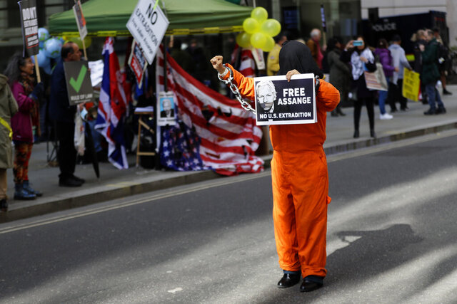 A demonstrator holds a banner outside the Old Bailey in London, Thursday, Oct. 1, 2020, as the Julian Assange extradition hearing to the US continues. (AP Photo/Kirsty Wigglesworth)