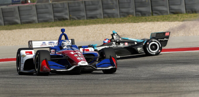 Tony Kanaan (14), of Brazil, passes Colton Herta (88) as spins out on a turn during a practice session for the IndyCar Classic auto race, Friday, March 22, 2019, in Austin, Texas. (AP Photo/Eric Gay)