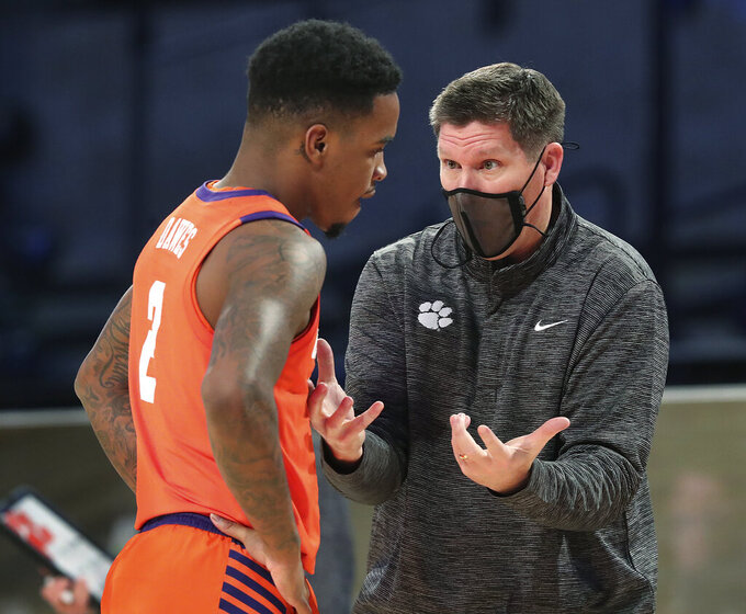 Clemson head coach Brad Brownell talks to guard Al-Amir Dawes during the team's NCAA college basketball game against Georgia Tech on Wednesday, Jan. 20, 2021, in Atlanta. (Curtis Compton/Atlanta Journal Constitution via AP, Pool)
