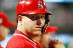 Los Angeles Angels designated hitter Mike Trout looks from the dugout as he waits to bat against the Texas Rangers during the eighth inning of a baseball game Monday, April 15, 2019, in Arlington, Texas. (AP Photo/Michael Ainsworth)