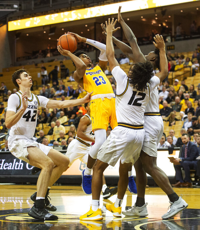 Morehead State's Malik Riddle, center, shoots between Missouri's Parker Braun, left, and Dru Smith (12) and Mitchell Smith, right, during the first half of an NCAA college basketball game Wednesday, Nov. 20, 2019, in Columbia, Mo. (AP Photo/L.G. Patterson)