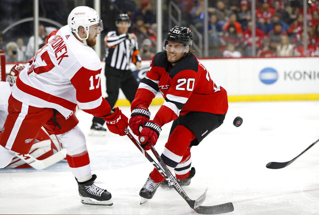New Jersey Devils center Blake Coleman (20) blocks as Detroit Red Wings defenseman Filip Hronek (17) tries to flip the puck to a teammate during the second period of an NHL hockey game, Thursday, Feb. 13, 2020, in Newark, N.J. (AP Photo/Kathy Willens)