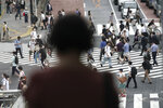 People wearing a protective face mask to help curb the spread of the coronavirus walk at Shibuya pedestrian crossing Thursday, July 9, 2020, in Tokyo.  The Japanese capital has confirmed more than 220 new coronavirus infections, exceeding its previous record.(AP Photo/Eugene Hoshiko)
