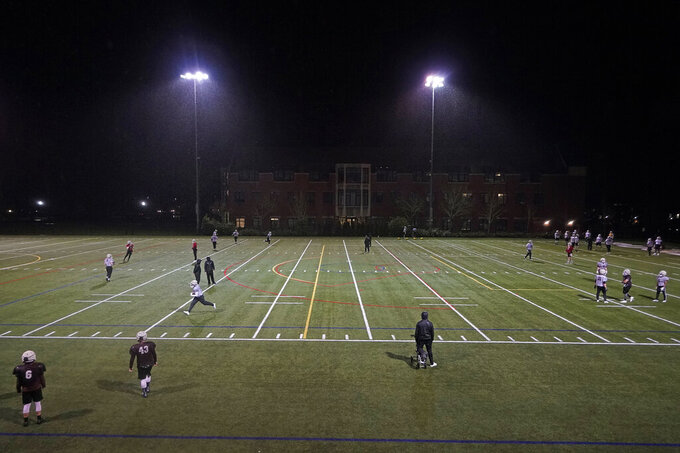 Players take part in drills under lights at the University of Puget Sound, Tuesday, Feb. 2, 2021, in Tacoma, Wash. For all the attention heaped on the FBS level of college football last fall as it tried to play, it will not be the only college football during the 2020-21 sports calendar as a handful of NCAA Division III and NAIA programs begin some form of a winter/spring season Saturday, Feb. 6. (AP Photo/Ted S. Warren)