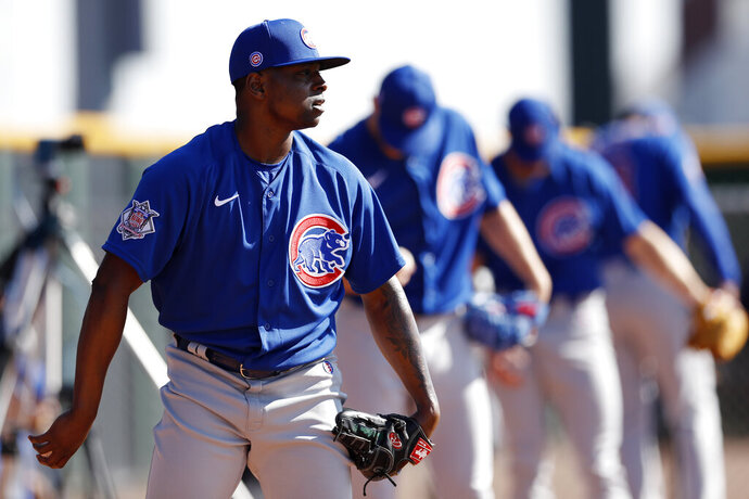 Chicago Cubs pitcher Jharel Cotton, left, throws alongside other pitchers during a spring training baseball workout Wednesday, Feb. 12, 2020, in Mesa, Ariz. (AP Photo/Gregory Bull)
