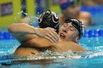 Chase Kalisz hugs Jay Litherland after winning Men's 400 Individual Medley during wave 2 of the U.S. Olympic Swim Trials on Sunday, June 13, 2021, in Omaha, Neb. (AP Photo/Jeff Roberson)