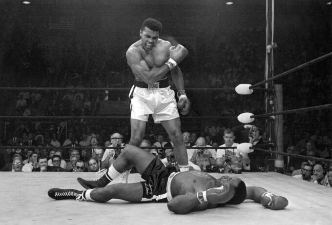 FILE - Heavyweight champion Muhammad Ali stands over fallen challenger Sonny Liston, shouting and gesturing shortly after dropping Liston with a short hard right to the jaw on May 25, 1965, in Lewiston, Maine. The legendary boxer and activist gets the Ken Burns treatment in a four-part film premiering Sept. 19 on PBS. (AP Photo/John Rooney, File)