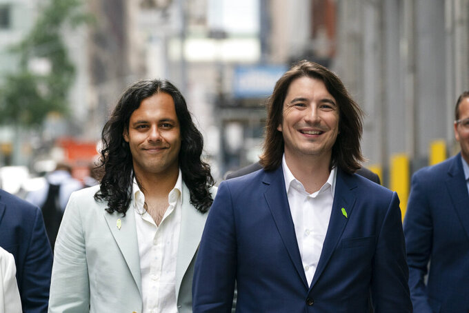Vladimir Tenev, CEO and co-founder of Robinhood, right, walks in New York's Times Square with Baiju Bhatt, also co-founder, following their company's IPO, Thursday, July 29, 2021. Robinhood is selling its own stock on Wall Street, the very place the online brokerage has rattled with its stated goal of democratizing finance. Through its app, Robinhood has introduced millions to investing and reshaped the brokerage industry, all while racking up a long list of controversies in less than eight years. (AP Photo/Mark Lennihan)