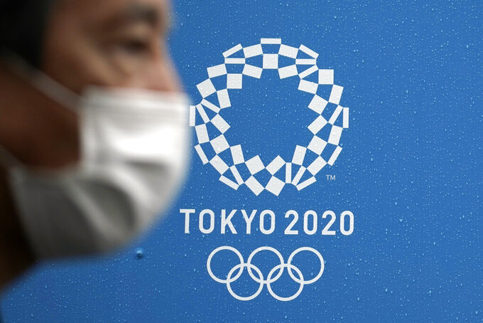 A man wearing a face mask to help curb the spread of the coronavirus walk past a logo of Tokyo 2020 Olympics in Tokyo on Oct. 8, 2020. The torch relay is kicking off from northeastern Japan. It will last 121 days and involve 10,000 runners carrying the torch to 47 Japanese prefectures. (AP Photo/Eugene Hoshiko)