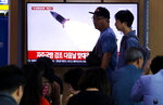 People pass by a TV showing a file image of North Korea's missile launch during a news program at the Seoul Railway Station in Seoul, South Korea, Wednesday, Oct. 2, 2019. North Korea on Wednesday fired projectiles toward its eastern sea, South Korea's military said, in an apparent display of its expanding military capabilities ahead of planned nuclear negotiations with the United States this weekend. The sign reads: