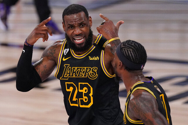 Los Angeles Lakers forward LeBron James talks with guard Kentavious Caldwell-Pope during the first half in Game 5 of basketball's NBA Finals against the Miami Heat Friday, Oct. 9, 2020, in Lake Buena Vista, Fla. (AP Photo/Mark J. Terrill)