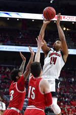 Louisville forward Dwayne Sutton (24) shoots over Miami (Ohio) guard Dae Dae Grant (3) and guard Milos Jovic (15) during the second half of an NCAA college basketball game in Louisville, Ky., Wednesday, Dec. 18, 2019. Louisville won 70-46. (AP Photo/Timothy D. Easley)