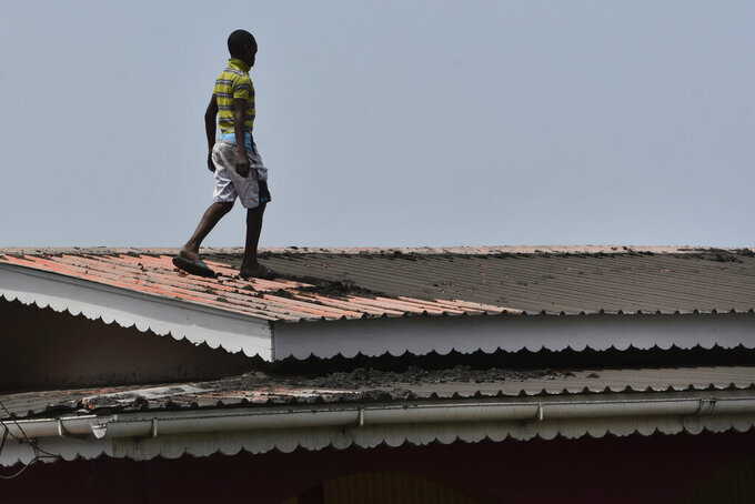 A youth walks on the roof of a home covered in volcanic ash after La Soufriere volcano erupted, in Wallilabou on the western side of the Caribbean island of St. Vincent, Monday, April 12, 2021. (AP Photo/Orvil Samuel)
