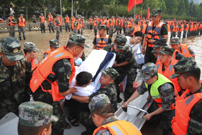 Chinese military personnel evacuate residents from a hospital where about 3,000 people were trapped by the flood in Zhengzhou in central China's Henan province Thursday, July 22, 2021. Residents of the storm-ravaged central Chinese city of Zhengzhou on Thursday were shoveling mud from their homes and hauling away wrecked cars and piles of destroyed belongings following floods that killed at least 33 people in the city and surrounding areas. (Chinatopix Via AP) CHINA OUT