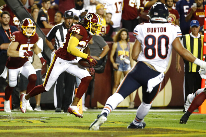 Washington Redskins cornerback Josh Norman (24) runs with his interception in front of Chicago Bears tight end Trey Burton (80) during the second half of an NFL football game Monday, Sept. 23, 2019, in Landover, Md. (AP Photo/Patrick Semansky)