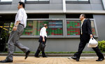People walk past an electronic stock board of a securities firm in Tokyo, Thursday, June 14, 2018. Asian stock markets slumped on Thursday with South Koreans stocks plunging 1.6 percent on the first day of trading after an unprecedented summit between leaders of North Korea and the United States. Stocks plunged after Federal Reserved hiked its key rate and signaled an acceleration in its pace of rate increase. (AP Photo/Shuji Kajiyama)
