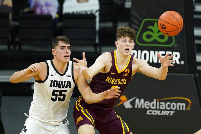 Minnesota center Liam Robbins catches a pass in front of Iowa center Luka Garza (55) during the second half of an NCAA college basketball game, Sunday, Jan. 10, 2021, in Iowa City, Iowa. Iowa won 86-71. (AP Photo/Charlie Neibergall)