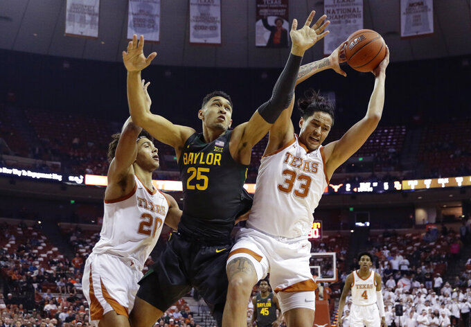 Baylor forward Tristan Clark (25) battles Texas forwards Kamaka Hepa (33) and Jericho Sims (20) for a rebound during the first half of an NCAA college basketball game, Monday, Feb. 10, 2020, in Austin, Texas. (AP Photo/Eric Gay)