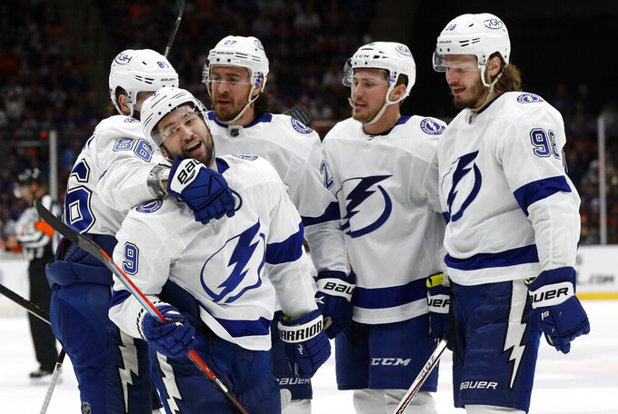Tampa Bay Lightning center Tyler Johnson (9) celebrates his third-period goal against the New York Islanders with right wing Nikita Kucherov (86), defenseman Ryan McDonagh (27), left wing Ross Colton (79) and defenseman Mikhail Sergachev (98) in Game 4 of an NHL hockey semifinal Saturday, June 19, 2021, in Uniondale, N.Y. (AP Photo/Jim McIsaac)