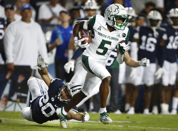 South Florida wide receiver Jimmy Horn Jr. (5) tries to run past BYU running back Sione Finau (20) in the first half of an NCAA college football game Saturday, Sept. 25, 2021, in Provo, Utah. (AP Photo/George Frey)