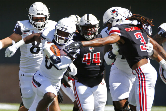 Cincinnati running back Charles McClelland, left, breaks through the line of scrimmage against Austin Peay defensive back Johnathon Edwards during the first half of an NCAA college football game Saturday, Sept. 19, 2020, in Cincinnati, Ohio. (AP Photo/Jay LaPrete)