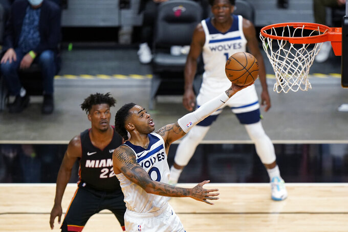 Minnesota Timberwolves guard D'Angelo Russell (0) goes up to shoot as Miami Heat forward Jimmy Butler (22) and guard Anthony Edwards (1) look on during the first half of an NBA basketball game, Friday, May 7, 2021, in Miami. (AP Photo/Wilfredo Lee)