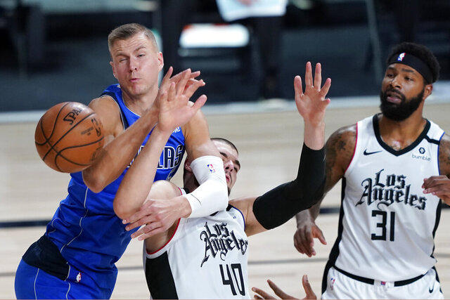 Dallas Mavericks' Kristaps Porzingis, left, battles Los Angeles Clippers' Ivica Zubac (40) during the first half of an NBA basketball first round playoff game Friday, Aug. 21, 2020, in Lake Buena Vista, Fla. (AP Photo/Ashley Landis, Pool)