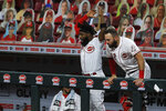 Cincinnati Reds' Brian Goodwin, left, and Curt Casali, right, react to the two-run home run hit by Eugenio Suarez in the sixth inning during a baseball game against the Milwaukee Brewers in Cincinnati, Monday, Sept. 21, 2020. (AP Photo/Aaron Doster)