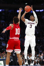 Connecticut guard Alterique Gilbert (3) shoots a 3-pointer with Indiana guard Rob Phinisee (10) defending him during the first half of an NCAA college basketball game in the Jimmy V Classic, Tuesday, Dec. 10, 2019, in New York. (AP Photo/Kathy Willens)