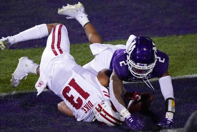Wisconsin wide receiver Chimere Dike, left, misses the catch against Northwestern defensive back Greg Newsome II, during the second half of an NCAA college football game in Evanston, Ill., Saturday, Nov. 21, 2020. Northwestern won 17-7. (AP Photo/Nam Y. Huh)