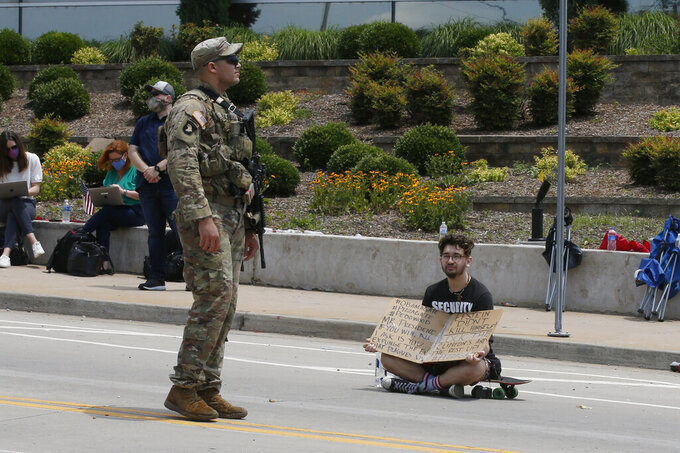 FILE - In this Saturday, June 20, 2020 file photo, a President Donald Trump supporter sits with a sign next to a National Guardsman providing security at the BOK Center for a Trump rally in Tulsa, Okla.  On Friday, June 26, 2020, The Associated Press reported on a photo circulating online incorrectly claiming it shows a massive crowd in a parking lot at Trump's rally in Tulsa, on Saturday. The mis-identified photo shows an event in Arlington, Va., not Trump's rally in Tulsa. (AP Photo/Sue Ogrocki)