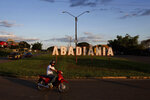 In this Jan. 3, 2019 photo, a man rides his motorcycle past the white block letters that spell out the name of the city, in Abadiania, Brazil, the home of spiritual healer Joao Teixeira de Faria. For over 40 years, de Faria drew people from all over the world to this small dirt in central Brazil, offering treatment for everything from depression to cancer. (AP Photo/Eraldo Peres)