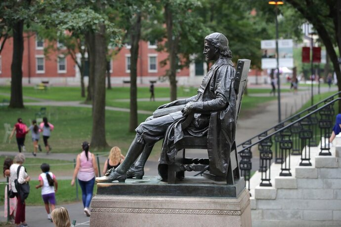 FILE - In this Aug. 13, 2019, file photo, the statue of John Harvard sits in Harvard Yard at Harvard University in Cambridge, Mass. Federal prosecutors on Tuesday, Jan. 28, 2020, charged Harvard University professor Charles Leiber, chair of the department of chemistry and chemical biology, with lying to officials about his involvement with a Chinese government-run recruitment program through which he received tens of thousands of dollars. (AP Photo/Charles Krupa)