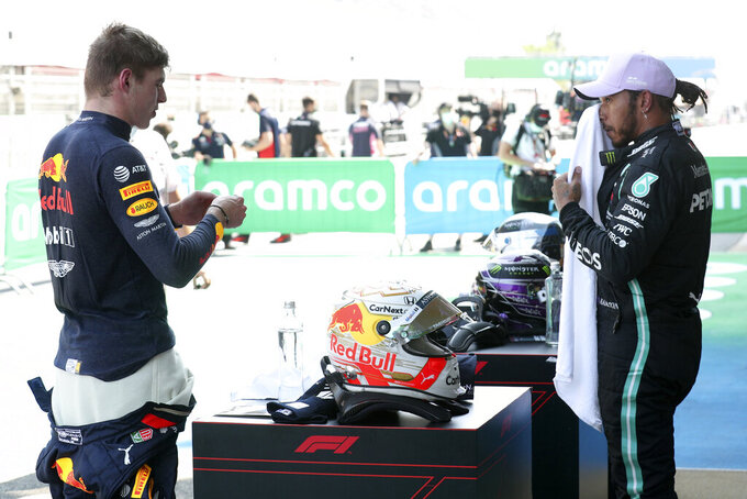 Red Bull driver Max Verstappen of the Netherlands, left, talks to Mercedes driver Lewis Hamilton of Britain after the qualifying prior to the Formula One Grand Prix at the Barcelona Catalunya racetrack in Montmelo, Spain, Saturday, Aug. 15, 2020. (Albert Gea, Pool via AP)