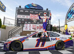Denny Hamlin stands on his car after winning the NASCAR Cup Series auto race at Dover International Speedway, Saturday, Aug. 22, 2020, in Dover, Del. (AP Photo/Jason Minto)