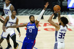 Los Angeles Clippers guard Paul George (13) defends against Sacramento Kings forward Marvin Bagley III (35) during the third quarter of an NBA basketball game Wednesday, Jan. 20, 2021, in Los Angeles. (AP Photo/Ashley Landis)