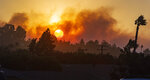 In this view from Newport Boulevard in North Tustin, the morning sun rises through the smoke of fire in the canyons east of North Tustin on Monday, Oct. 26, 2020. Firefighters were aggressively battling a vegetation fire that broke out in the hills near Silverado in Orange County as strong wind gusts pushed it. (Mark Rightmire/The Orange County Register via AP)