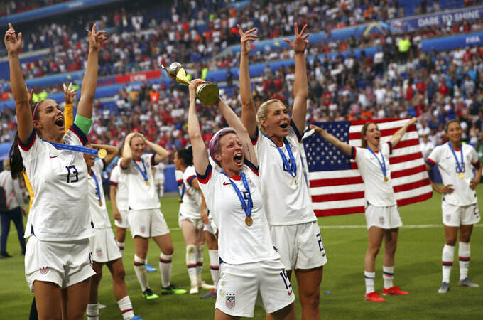 FILE- In this July 7, 2019, file photo, United States' Megan Rapinoe, center, holds the trophy as she celebrates with teammates after they defeated the Netherlands 2-0 in the Women's World Cup final soccer match at the Stade de Lyon in Decines, outside Lyon, France. (AP Photo/Francisco Seco, File)