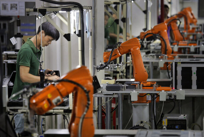 FILE - In this Aug. 21, 2015 file  photo, a man works amid orange robot arms at Rapoo Technology factory in southern Chinese industrial boomtown of Shenzhen.  China issued an outline Friday, Nov. 15, 2019,  of policies aimed at promoting high-tech manufacturing after it stopped pushing a strategy that helped trigger a tariff war with Washington. A statement by the Cabinet's planning agency called for the government to help manufacturers in autos, electronics and other fields. It gave few details about how to carry that out or whether it will involve diplomatically contentious market barriers or subsidies. (AP Photo/Vincent Yu, File)